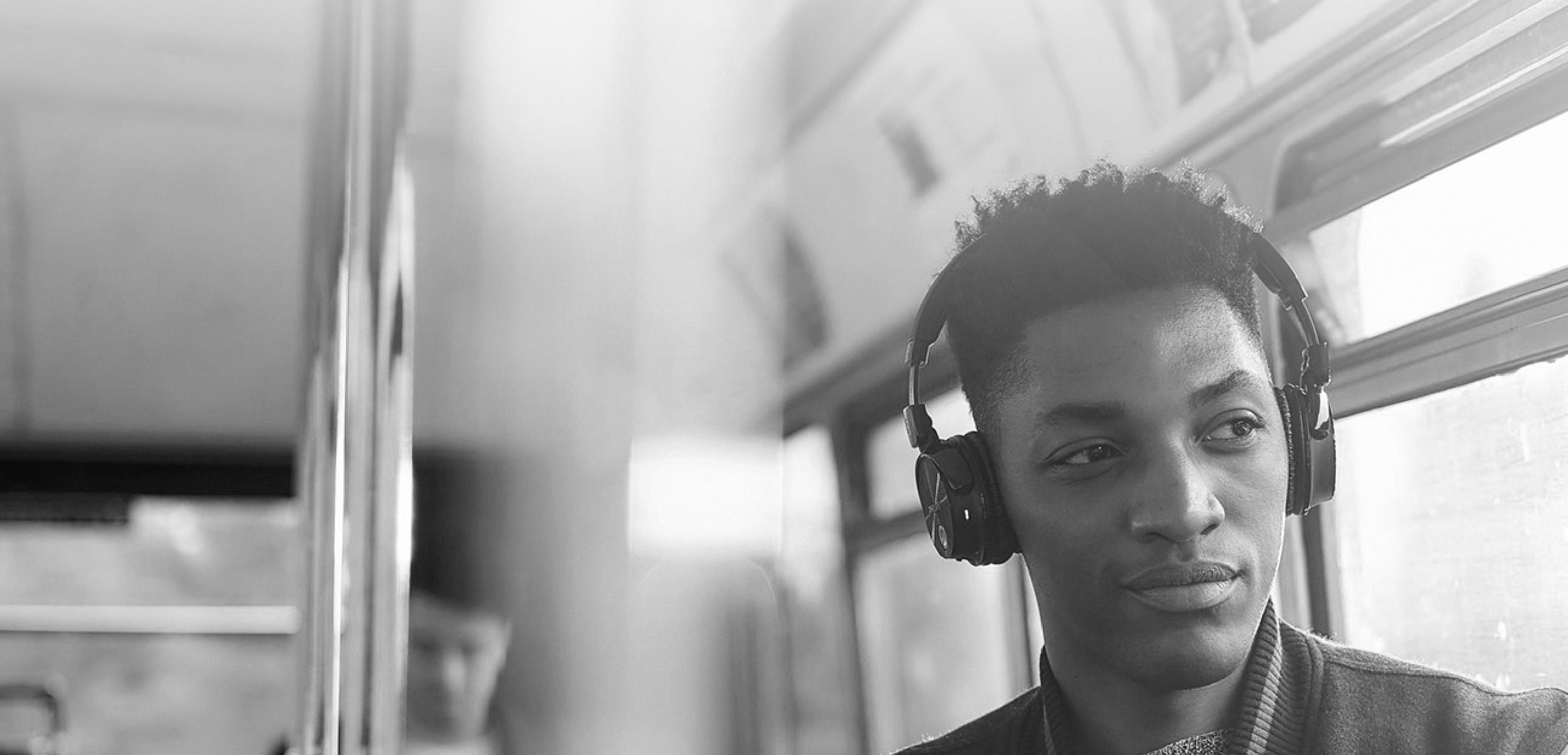 Man on London bus listening to digital audio through headphones