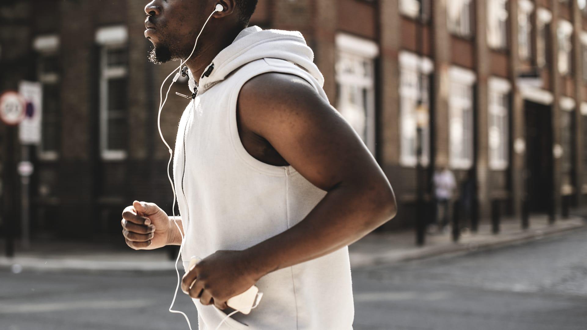 Man jogging through London listening to radio through headphones