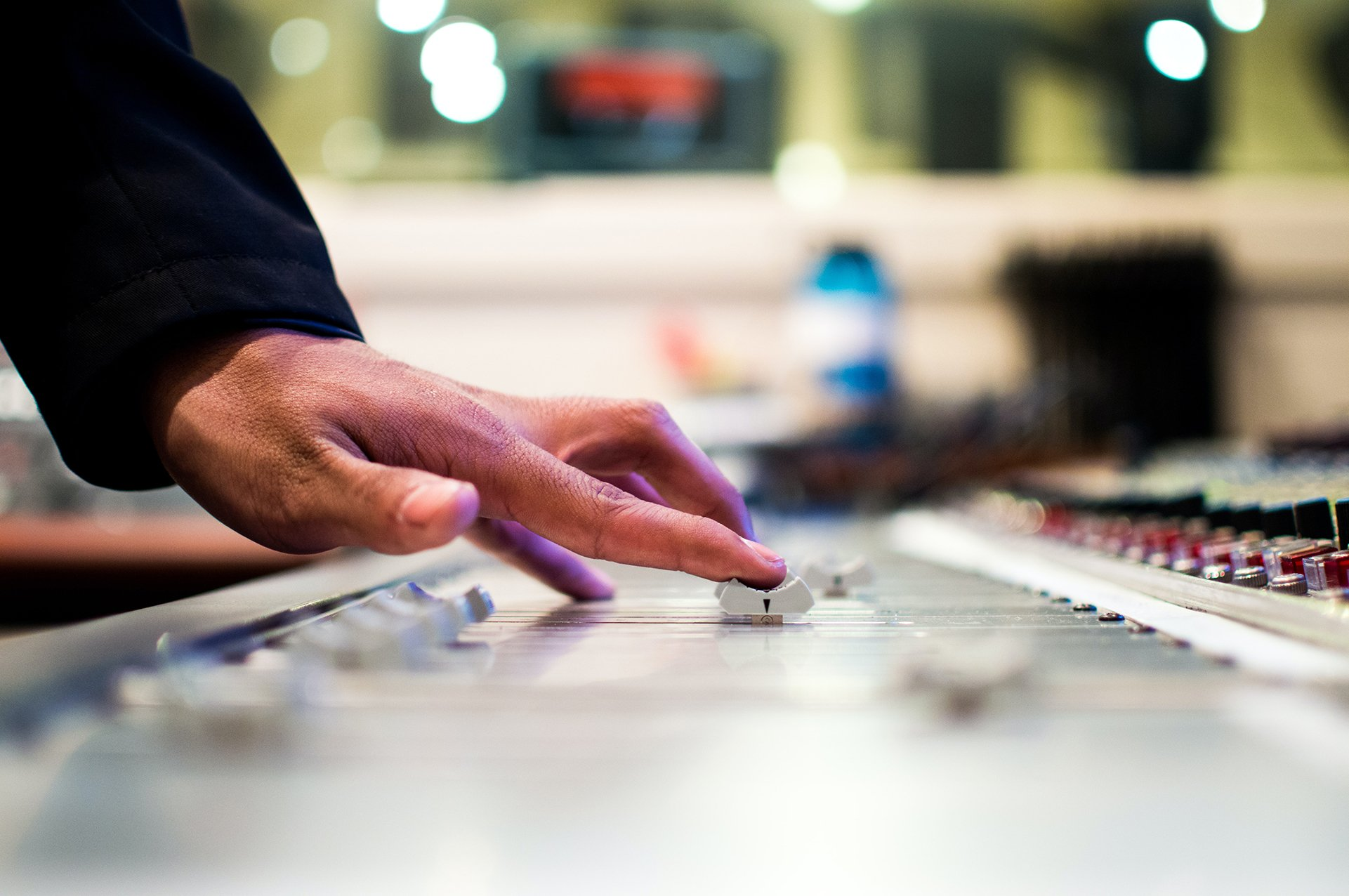 Audio producer's hand on a mixing desk fader